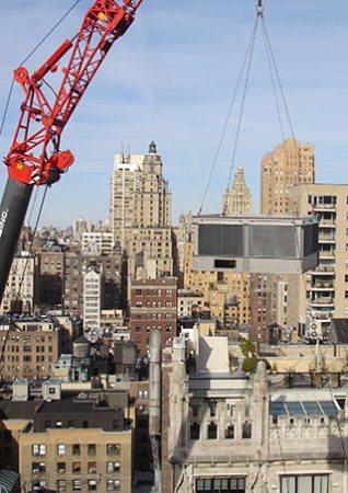 Crane lifting HVAC equipment