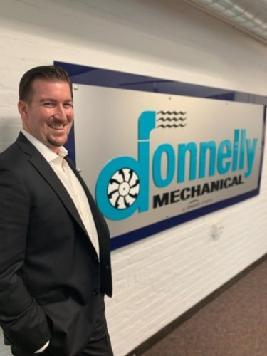 VP Thomas Cahil standing in front of the Donnelly Mechanical sign