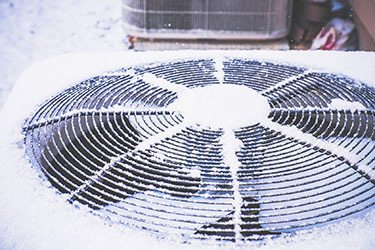 air conditioning unit covered in fresh snow